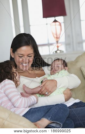 Mother sitting on sofa with daughters