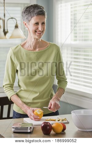 Senior woman cutting fruit