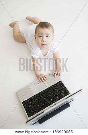 Mixed race baby boy playing with laptop