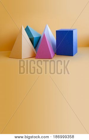Colorful solid figures still life background. Three-dimensional prism pyramid rectangular cube objects on orange. Yellow blue pink green colored geometric shapes, soft focus photo. Copy space.