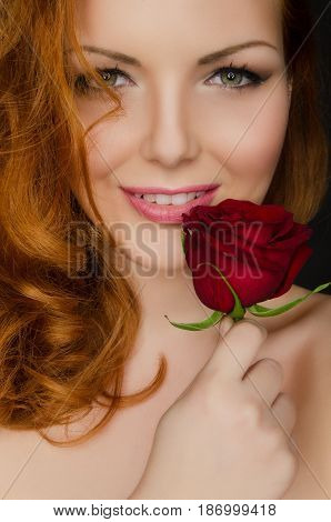 Young woman with red hair holds red rose in her hands