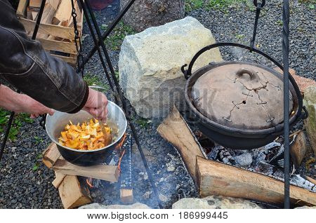 Preparing mushrooms and venison goulash on an open fire in a kettle blending chopped onion Chanterelle by wooden ladle