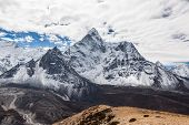 Beautiful view of Ama Dablam mountain summit on the famous Everest Base Camp trek in Himalayas Nepal. Snowy mountain summit on a cloudy day. Panoramic mountain summit landscape. poster