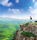 Girl on the peak of mountain. Landscape composition. poster