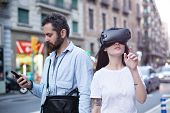 Authentic and trendy couple of millenials use augmented reality technology and VR headset in the busy city street poster