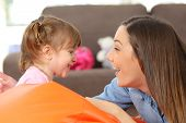 Side view portrait of a happy mother and 2 years baby daughter facing and joking in the living room at home poster