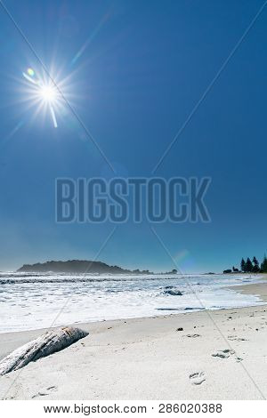 Footprints in sand past log with turbulent sea during strong ocean surge with Moturiki Island at end of beach poster