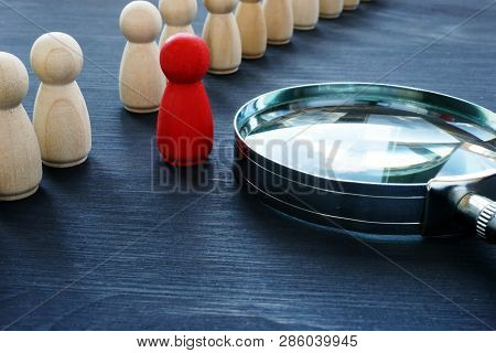 Identify concept. Recruitment and talent management. Red figurine and magnifier. poster