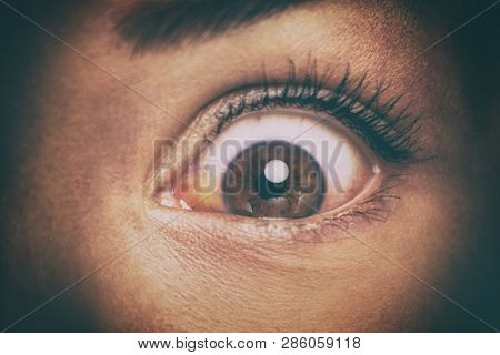 Eye peeking through peep hole watching something scary. Scared woman with look of horror in her eyes looking peeping from a dark room at night.