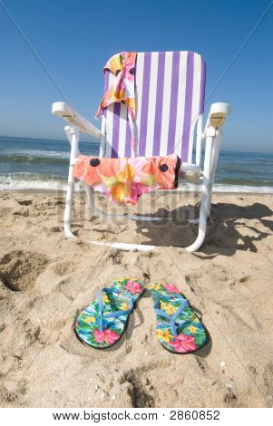 Beach Chair And Sandals In The Sand