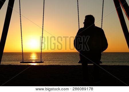 Back View Backlighting Silhouette Of A Man Alone On A Swing Looking At Empty Seat At Sunset On The B