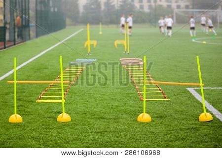 Soccer Field With Training Equipment And Fence In Background. Junior Football Team Training With Coa