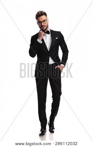 Ellegant man arranges his bow-tie with a hand in his pocket while standing