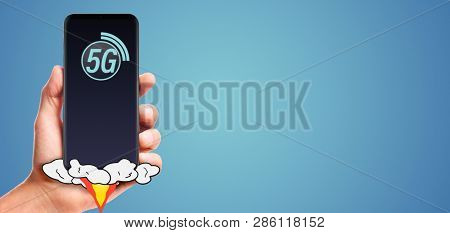 male hand hold launching 5G smartphone, on blue background.
