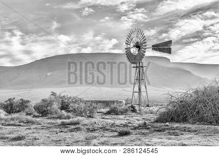 An Early Morning Landscape, With A Windmill And Dam, In The Tankwa Karoo Of South Africa. Monochrome