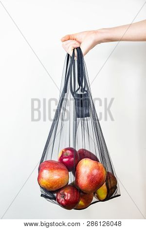 Holding A Reusable String Bag Full Of Apples. Sustainable Eco Packaging Concept: Shopping For Grocer