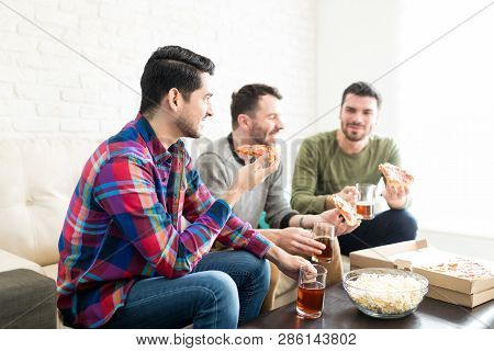 Handsome Young Man Wearing Casuals While Having Pizza And Beer With Pals In Living Room