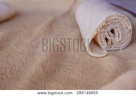 Injera is a sourdough flatbread made from teff flour.  It is the national dish of Ethiopia, Eritrea, Somalia and Djibouti poster