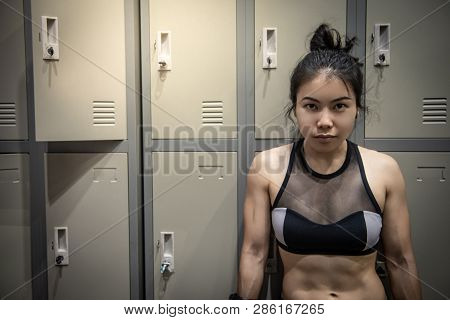 Confident Asian Woman Boxer With Boxing Gloves Standing By The Locker Cabinet In Locker Room. Female