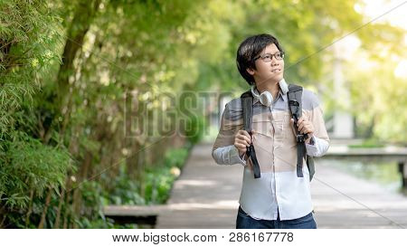 Confident Asian Man University Student With Glasses And Headphones Smiling And Holding Backpack In T