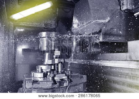 The process of drilling and grinding holes in the body of the valve on the CNC machine. Yellow-green coolant splashes into place poster