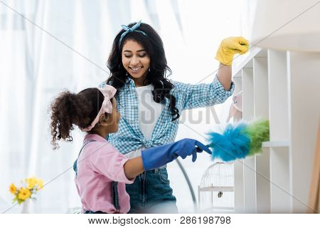 smiling african american mother and daughter cleaning shelves with dusters poster