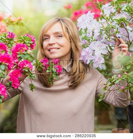 Beautiful Woman Gardening In Greenhouse. Florist Working And Taking Care Of The Plants And Flowers.