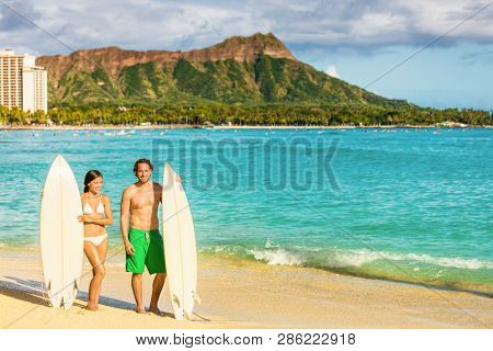 Hawaii surf couple on waikiki beach in Honolulu, Hawaii. Summer holidays travel destination young people relaxing. Healthy active lifestyle.