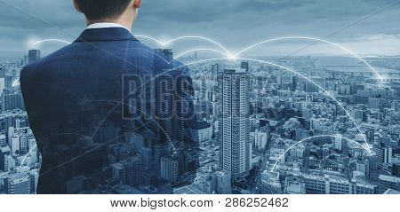 Businessman In Blue Suit Looking At Cityscape With Network Connection In The City. Business Network