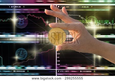 Closeup Hand Holding Bitcoin Over The Cryptocurrency Trading Screen, Bitcoin Exchange Screen Of Trad