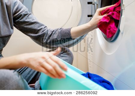 Picture of woman hands putting dirty clothes in washing machine.