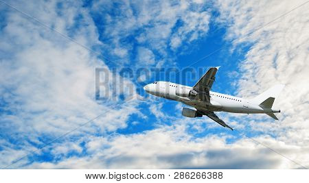 Airplane flying in the sky - travel background. Flying airplane, concept of air travel, commercial airplane in the flight. White flying airplane, travel concept