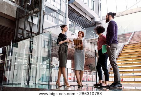 Group Of Young Businesspeople Standing Near A Staircase, Talking.