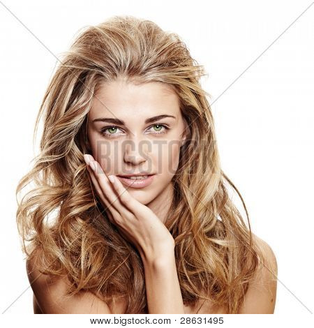 beautiful smiling woman with long blond curly hair and natural make-up on white background touching her face
