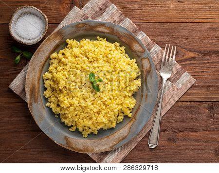Bulgur Wheat. Boiled Bulghur Cereal In Plate On Brown Wooden Table. Healthy Vegetarian Food, Top Vie