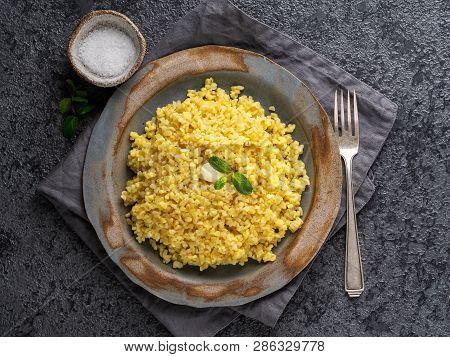 Bulgur Wheat. Boiled Bulghur Cereal In Plate On Dark Grey Stone Table. Healthy Vegetarian Food, Top