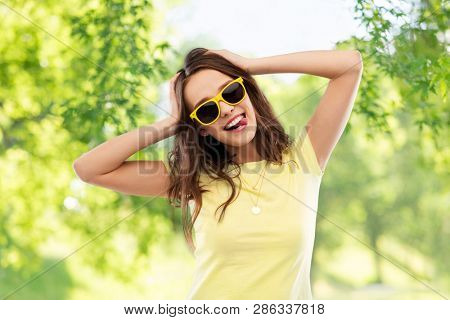 summer, accessory and people concept - smiling young woman or teenage girl in yellow t-shirt and sunglasses holding to her head over green natural background