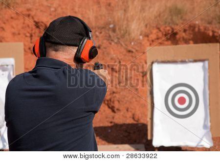 Man shooting at a target on an outdoor shooting range, focus on gun