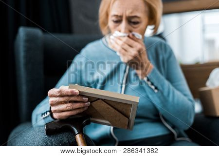 Grieving Senior Woman Crying And Wiping Face From Tears With Tissue While Looking At Picture Frame