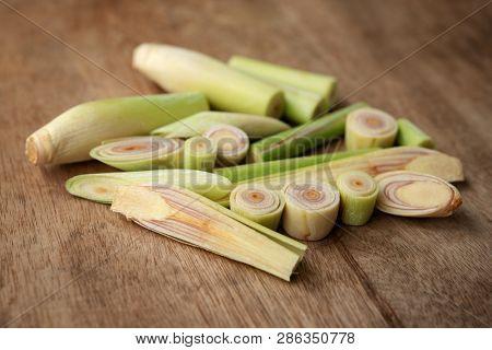Fresh green lemongrass slices on wooden background.