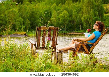 Mature Woman Enjoying Nature Landscape, Sitting On Chair On Lake Fjord Shore. Holidays Relaxation An