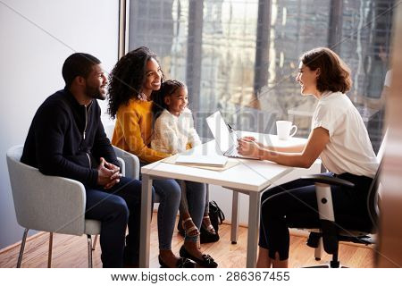 Family Having Consultation With Female Pediatrician In Hospital Office