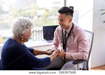Male Doctor In Office Reassuring Senior Female Patient And Holding Her Hands