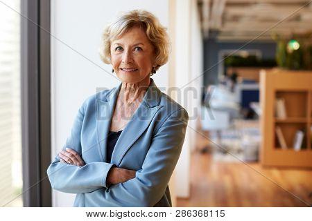 Portrait Of Smiling Senior Businesswoman In Modern Office Standing By Window