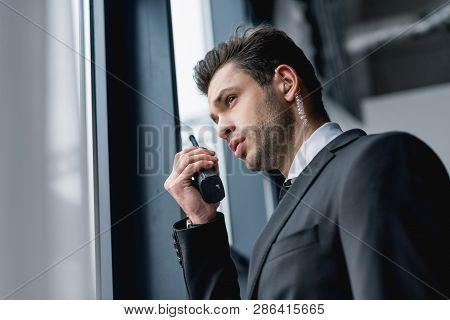View Of Handsome Bodyguard In Suit Using Walkie-talkie