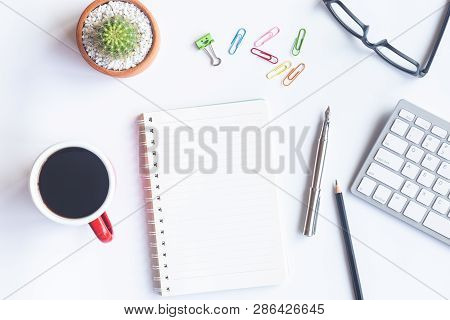 White Desk Office With Laptop, Smartphone And Other Work Supplies With Cup Of Coffee. Top View With