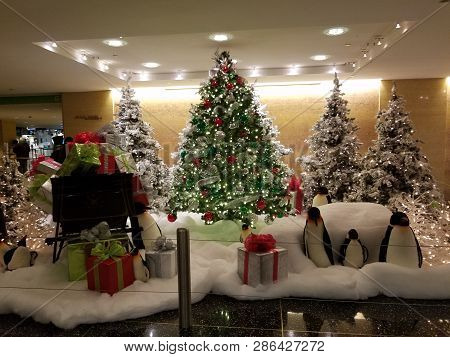 Christmas Trees Adorned With Lights And Ornaments, A Sleigh Filled With Presents And Stuffed Penguin
