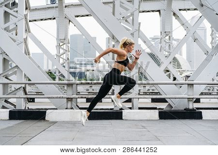 Side Motion View Of Runner Woman Sprinting In The City. Sport Lifestyle.