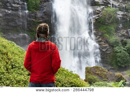 Woman In A Red Jacket Looking At The Waterfall. Tourism Concept