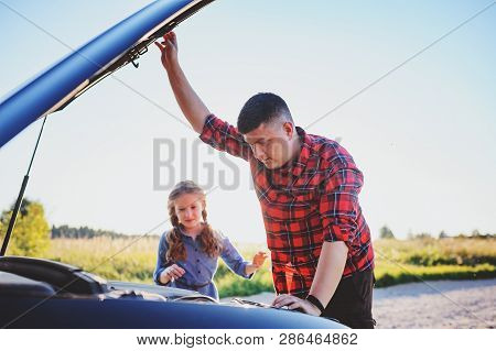 Father And Daughter Fixing Problems With Car During Summer Road Trip. Kid Girl Helping Dad.